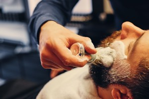 Close up image of barber shaving a man with a sharp steel razor.